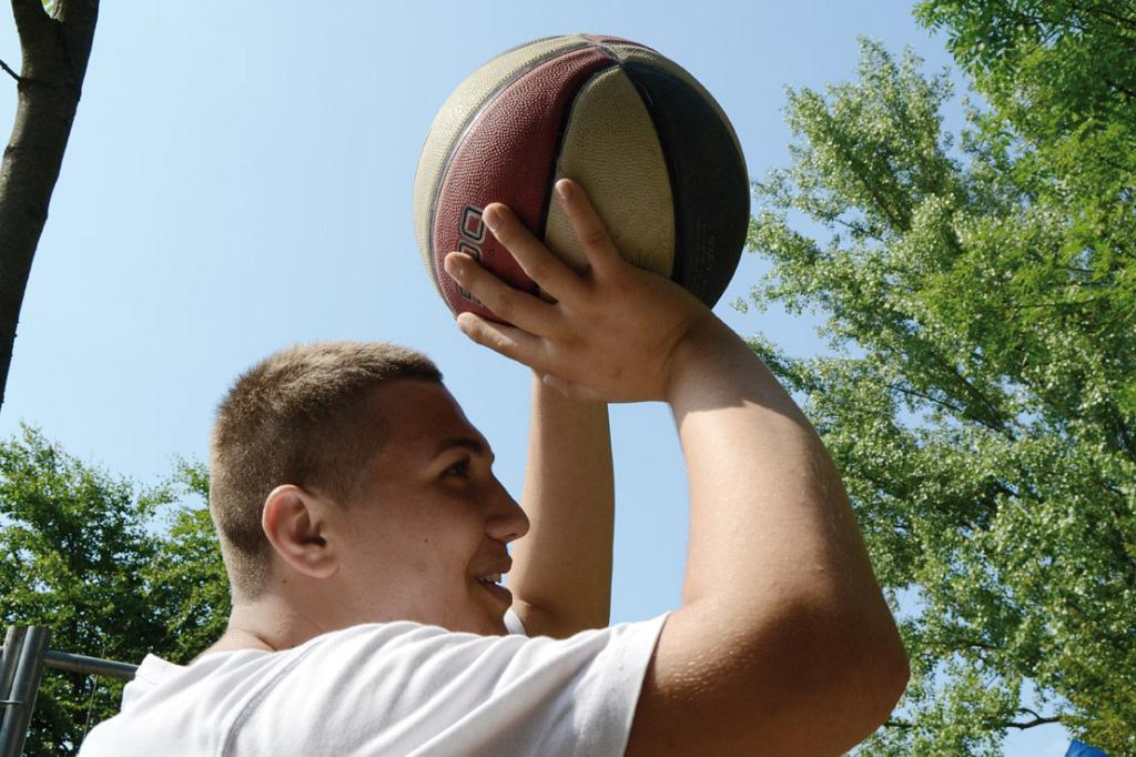 Jugendlicher bereit einen Basketball auf den Korb zu werfen