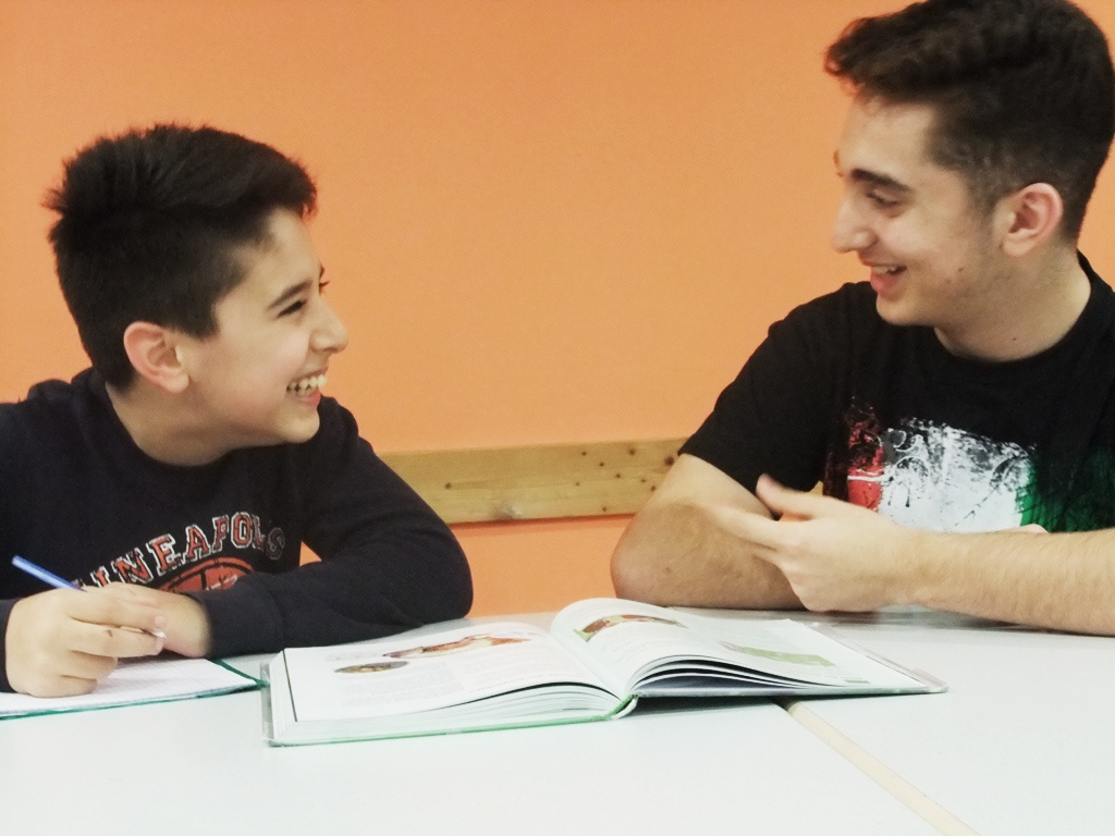 Jugendliche sitzen an einem Tisch und lernen. Sie lachen.