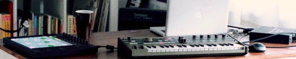 Ein Keyboard, ein Laptop und ein Mischpult stehen auf einem Tisch.