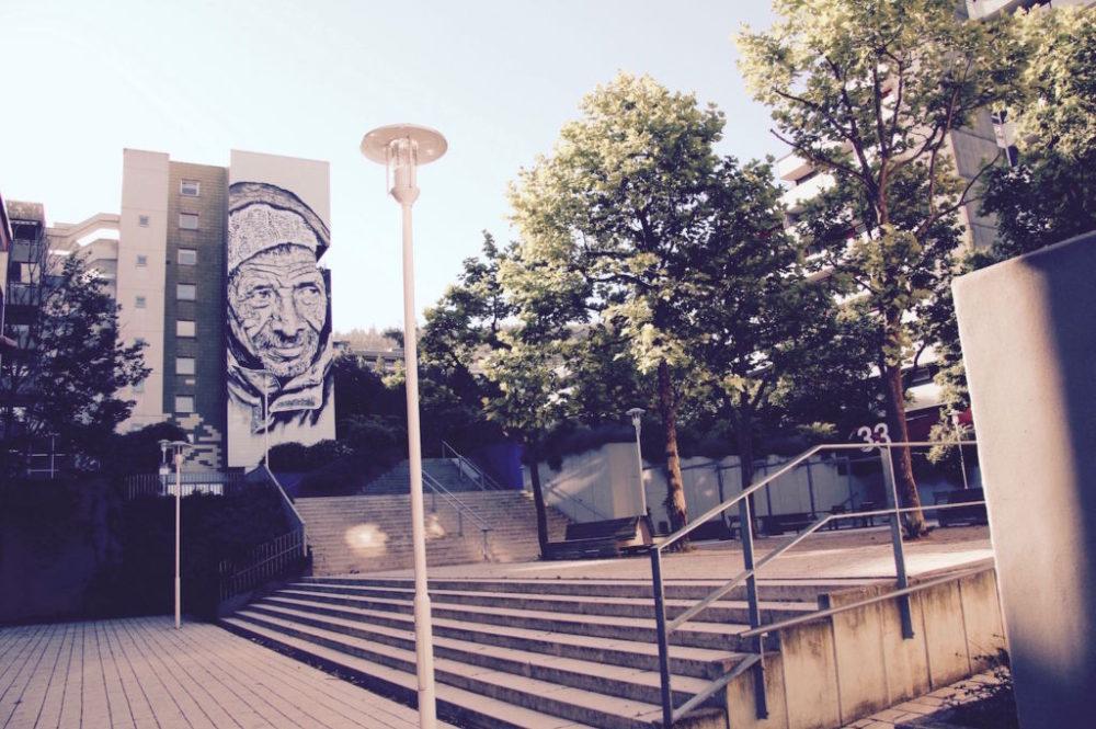 Eine breite Treppe führt zu einem Gebäude auf dem die Malerei eines Mannes großflächig über die ganze Wand zu sehen ist.