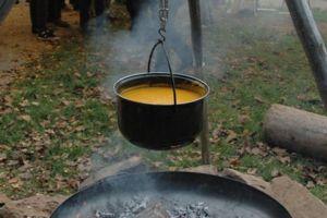 Sichere Feuerstelle. Darüber hängt ein Topf mit Suppe.
