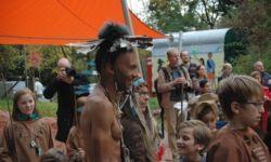 Ein Indianer steht lachend in der Menschenmenge