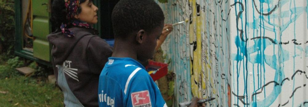 Künstlerin des Metropolink Festivals bemalt Bauwagen mit Kind
