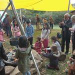 Kinder halten Stöcke ins Feuer und backen Stockbrot