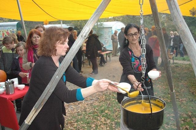 Frauen schöpfen Kürbisfarbene Suppe aus einem großen hängendem Topf