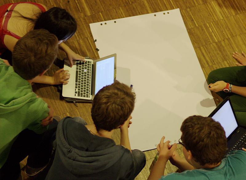 Jugendliche sitzen auf dem Boden und erarbeiten ein Thema mit unterschiedlichen Medien