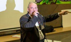 Ein Mann spricht ins Mikrofon und gestikuliert.