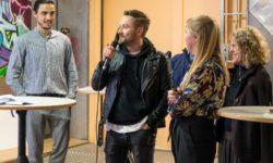 Mehrere Personen im Bild.. Ein Mann spricht ins Mikrofon.
