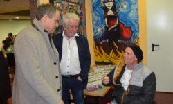 Drei Personen im Bild eine Person sitzt im Rollstuhl