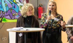 Zwei Frauen am Stehpult, eine spricht ins Mikrofon