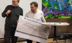 Eine Person am Mikrofon, eine hält den Scheck mit dem Wert von 6000 Euro